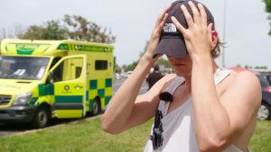 Jussi au pair seisoo katuvan näköisenä pidelleen päätään, taustalla ambulanssi.
