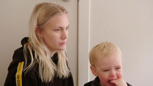 Ada au pair pienen itkevän pojan kanssa tuskastuneen näköisenä.