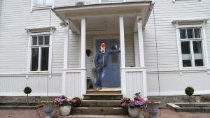 Man med keps och smårutig jacka lutar sig mot pelare på veranda.