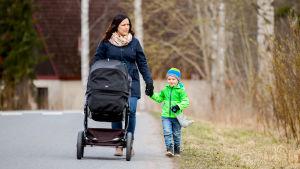 Jenniina Termonen kävelee työntäen lastenvaunuja. Vasemmasta kädestä pitää kiinni esikoispoika.