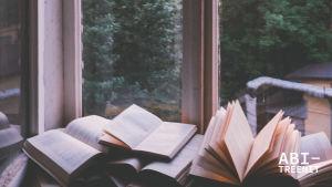 Artikkelikuva Abitreenien artikkeliin. Kuvassa pino avonaisia kirjoja ikkunalaudalla.