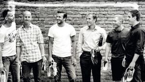 Manchester United -pelaajat David Beckham, Nicky Butt, Ryan Giggs, Paul Scholes, Phil ja Gary Neville vierekkäin tiiliseinän edessä nappiksen käsissään mustavalkoisessa kuvassa.