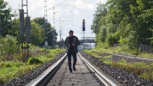 Markku Laakso går längs järnvägsspåret