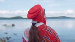 Saamelainen nainen seisoo rannalla selin kameraan.