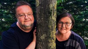 Toimittajat Risto Nordell ja Outi Paananen nojaavat puun runkoon ja katsovat kameraan.