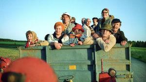 Hyvien ihmisten kylän ihmisiä traktorinlavalla.