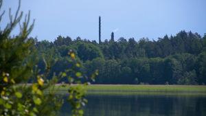 En bild på vatten med två skorstenar i bakgrunden