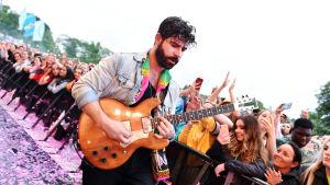 Foalsin laulaja-kitaristi soittaa kitaraa paineaidan edessä. taustalla yleisöä.