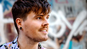 Eino Nurmisto seisoo graffitiseinän edessä katse suunnattuna kuvan oikeaan reunaan. Hän hymyilee.