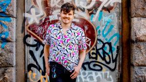 Bloggaaja Eino Nurmisto seisoo graffitiseinän edessä ja katsoo kameraan hymyillen. Hänellä on päällään värikäs paita, jossa on kirjaimia. Mustien farkkujen taskuista roikkuu aurinkolasit.