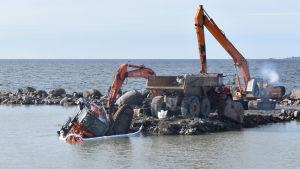 Flera orange arbetsmaskiner på en vågbrytare. En grävmaskin är halvt under vatten.