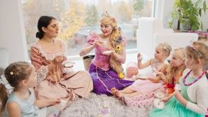 Lastensynttäreillä prinsessaksi pukeutunut Milja Korpela opettaa teen juontia.