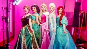 Viisi naista poseeraavaat eri Disney-prinsessojen asuissa.