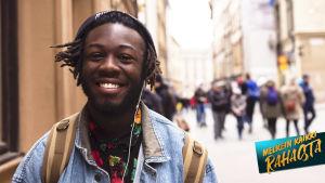 KUvassa mies hymyilee ja kävelee kadulla, katsoo kameraan