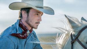 Nuori cowboy ratsastaa valkealla hevosella stetson päässään.