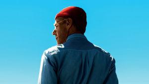 Jacques Cousteauta esittävä hahmo takaapäin kuvattuna. Miehellä päässä punainen pipo ja taustalla näkyy sininen taivas.