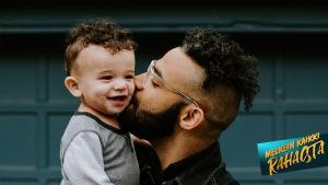Kuvassa lapsi isän sylissä.