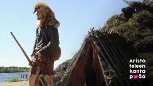 kivikautiseen asuun pukeutunut opas turvemajan edessä