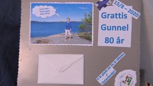 """Ett födelsedagskort med texten """"Grattis Gunnel 80 år"""" och """"Vi är glada att du är tillbaka i fosterlandet""""."""