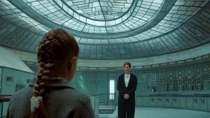 Pieni tyttö selkä kameraan seisoo naisen edessä huoneessa joka näyttää tieteiselokuvan operaatiohuoneelta.