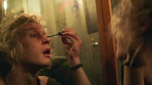 Henkilö laittaa peilin edessä ripsiväriä.