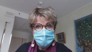 Lisa Enckells besöker sin mamma under coronaepidemin iförd munskydd.