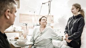 En mor sitter på en sjukhussäng och håller en vuxen dotter i handen.