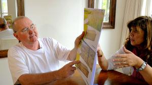 En man pekar i en broschyr med bagravningskistor. En kvinna sitter bredvid och ser på.