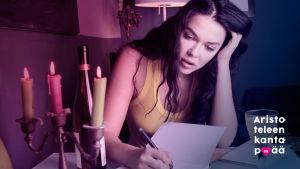 Nainen kirjoittaa kynttilän valossa päiväkirjaa.