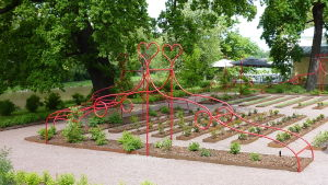 Röd skulptur av metall kring en trädgård.