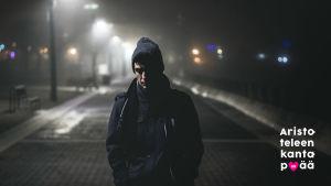 mies kävelee hämärällä kadulla