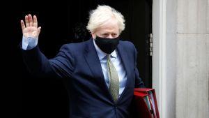 Storbritanniens premiärminister Boris Johnson bär munskydd då han lämnar sin tjänstebostad i London.