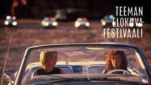 Thelma ja Louise istuvat autossa, takana näkyy poliisiautojen rivi. Kuva elokuvasta.
