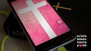 Raamatun päällä on kännykkä, jonka näytöllä risti