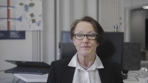 En kvinna sitter i ett kontor. Hon ser in i kameran och ser bestämd ut.
