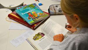 Lapsi lukee suomenkielistä kirjaa ja pöydällä on ruotsinkielisiä kirjoja. Kielikylpyluokka Vaasassa.