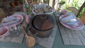 Ett dukat bord för två. På bordet finns bordstabletter, brödkorg och grytunderlägg gjorda av linfilt.
