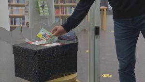 En hand sätter in ett julkort i en svart låda för att senare delas ut till ensamma äldre. I bakgrunden syns biblioteksböckr på hyllor.