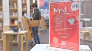 En röd skylt på ett bord gör reklam för kampanjen Julpost till åldringar. I bakgrunden syns en person med korg på armen som tittar på julkort i ett bibliotek.