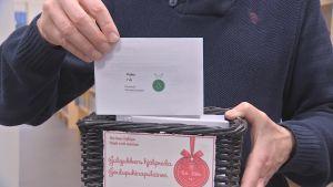 En person med blå tröja drar upp ett kort ur en liten låda med julklappsönskemål. På lappen står att en 7-årig pojke önskar sig små plastsoldater.