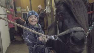 Tioåriga Lenni står glad tillsammans med en häst