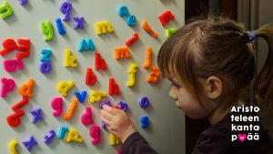 Tyttö järjestelee jääkaapin ovessa olevia magneettisia kirjaimia.
