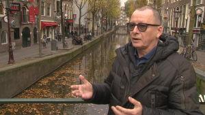 Invånaren Bert Nap står på en bro vid vid en av kanalerna i De Wallen. I bakgrunden ser man hur tomt det är på gatorna.