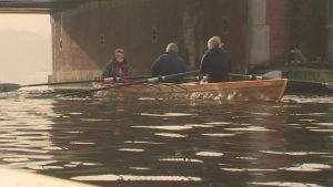 En roddbåt med tre personer i åker under en bro i Amsterdam.