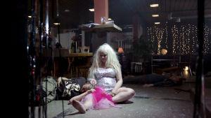 Paljettimekkoon pukeutunut Kristal (Katja Küttner) istuu ravintolan lattialla ja silittää sylissään makaavan miehen päätä. Kuva elokuvasta Kristal.