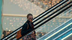 En kvinna med ett mönstrat munskydd står i en rulltrappa i ett köpcentrum.