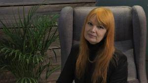 en kvinna med långt rött hår tittar in i kameran