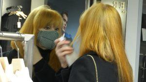 En kvinna med ansiktsmask speglar sig och rättar till håret.