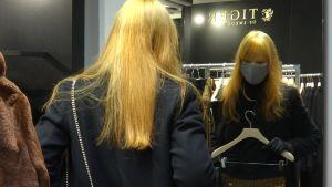 En kvinna poserar med ett plagg i hand framför en spegel i en affär.
