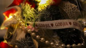 Närbild på julprydnader i en hög. Ett band med texten god jul syns bland krimskramset.